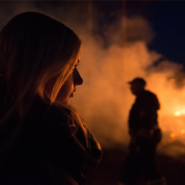 Are You Burning Up? Join Us To Discuss Into The Fire - Young woman looking at fire with man standing in the background